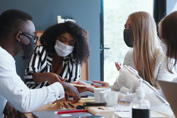 Four students wearing masks while working together.